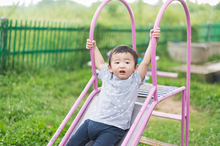 school yard: Little Asian kid playing slide at the playground under the sunlight in summer, Kids play on school yard. Happy kid in preschool. shallow DOF Stock Photo
