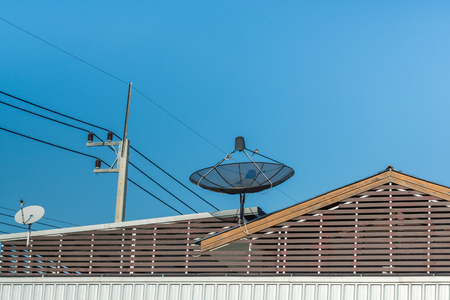 Big Black Satellite Dish on the roof with blue sky and cloud Stock Photo