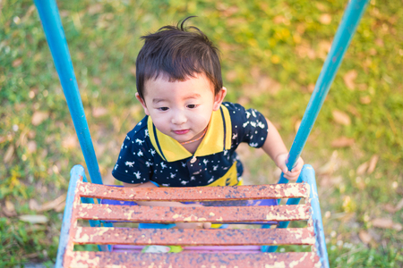 Asian kid goes up the stairs in the park. concept of growing up. step by step the child rises higher and goes further. under sunset light.