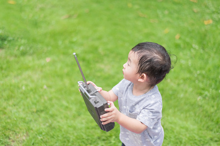 Little Asian kid holding a radio remote control (controlling handset) for helicopter , drone or plane at the playground, school yard. Happy kid in kindergarten or preschool.