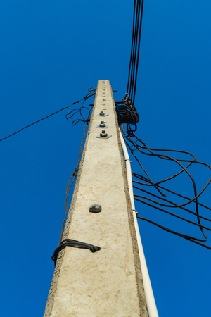 against the current: High voltage power pole with wires tangled on blue sky background. Stock Photo