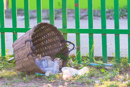 cesto basura: Weave trash basket, Dustbin made from bamboo weaving on grass field. fence background. under sun light.