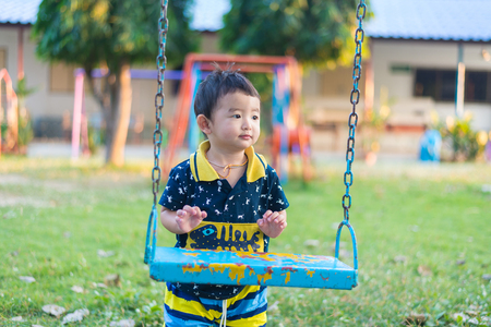 Young Asian boy play a iron swinging at the playground under the sunlight in summer, Kids play on school yard. Children having fun at daycare play ground.