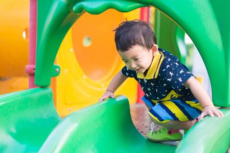 Weinig Aziatisch kind spelen dia bij de speelplaats onder de zon in de zomer, kinderen spelen op schoolplein. Gelukkig kind in kleuterschool. ondiepe DOF