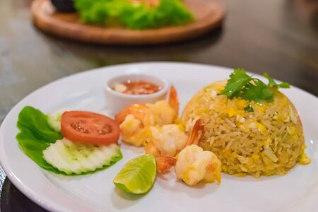 Interior room: Shrimp Fried Rice with vegetable in white dish on dark wood table. in dark room. under incandescent light. selective focus.