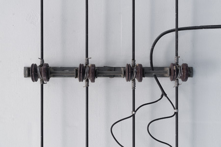 Power line and porcelain insulators with rack on white ceiling.