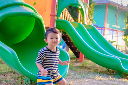 Little Asian kid playing slide at the playground under the sunlight in summer, Kids play on school yard. Happy kid in kindergarten or preschool. shallow Focus
