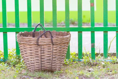 cesto basura: Weave trash basket, Dustbin made from bamboo weaving on grass field. fence background. Foto de archivo