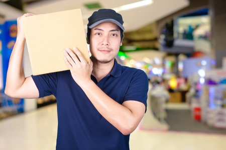 Asian smile Delivery man with cardboard box in hand standing in shopping mall or department store with blur bokeh background.