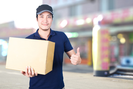 Asian smile Delivery man thumbs up with cardboard box in hand standing on blurred shop background.