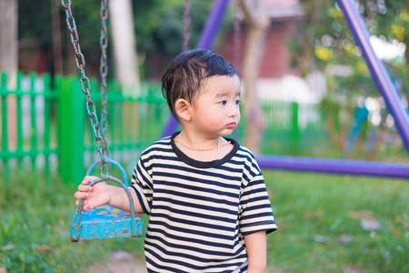Sad little Asian kid at the playground under the sunlight in summer, Kids play on school yard. shallow DOF