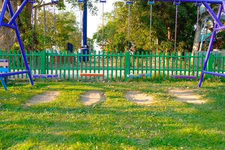 chain swing ride: Empty chain and metal swings in playground and meadow grass field under sun light in summer.