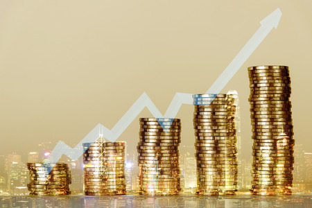 Double exposure of financial graph chart and rows of coins with blurred building background for finance and business concept, shallow focus Archivio Fotografico