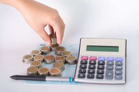 Stack of coins as house shape and calculator on the account book on white background. Concept for finance and banking, shallow focus