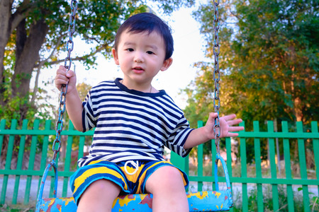 under ground: Young Asian boy play a iron swinging at the playground under the sunlight in summer, Kids play on school yard. Happy kid in kindergarten or preschool. Children having fun at daycare play ground. Stock Photo