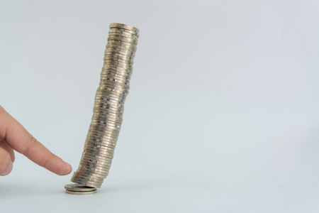 Finger pushing a pile of coins, column of coins falls , business crisis concept. shallow focus Reklamní fotografie