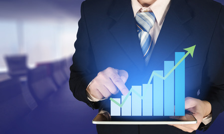 Double exposure businessman hand touching virtual panel of growth bar chart on financial graph chart and blurred meeting room, business success concept. Stockfoto