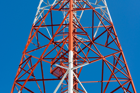 Mobile phone communication antenna tower with satellite dish on blue sky background, Telecommunication tower