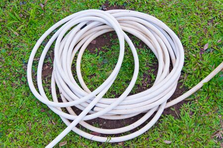 Garden hose or white rubber tube with faucet on grass field in garden. Stock Photo