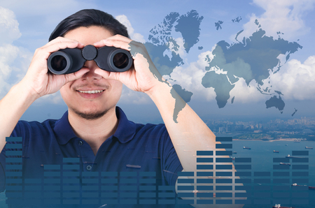 Double exposure of Asian investor with binoculars. Over seascape view from aerial and financial graph on blurred building background, import export concept, Elements of this image furnished by NASA. Stock Photo