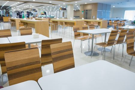 Interior of white table and wooden table on food court in shopping mall. food center in department store. shallow focus