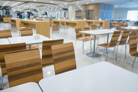 Interno della tavola bianca e tavola di legno su food court nel centro commerciale. centro alimentare nel grande magazzino. messa a fuoco superficiale Archivio Fotografico - 80751812