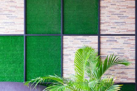 Muur van steen en kunstgrasachtergrond met metaalkader en palmboomdecoratie in rust ruimte.