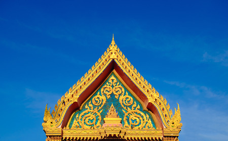 Gold color roof of buddhist temple with blue sky background. isosceles triangle shape.