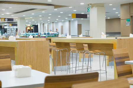 Interior of white table and wooden table on food court in shopping mall. food center in department store.