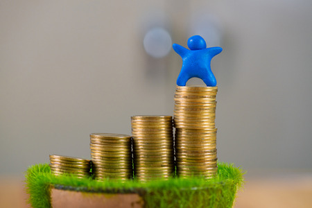 Miniature human figure made from blue plasticine with coins on wooden table. shallow focus, soft tone. business concept.
