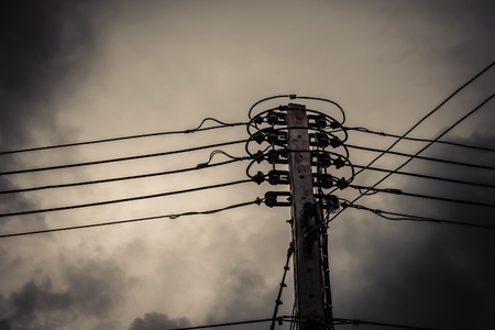 against the current: High voltage power pole with wires tangled on building background. vintage tone.