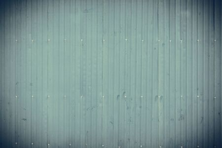 stainless: green corrugated metal wall or fence. background and texture. vintage tone.