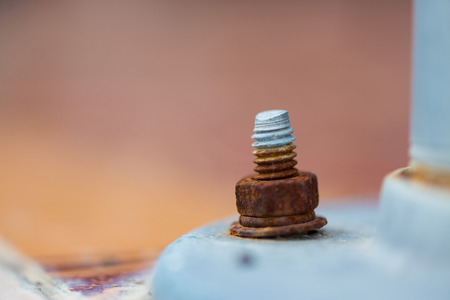 Old rusty steel bolt and nut with flat metal washer, selective focus. Stock Photo