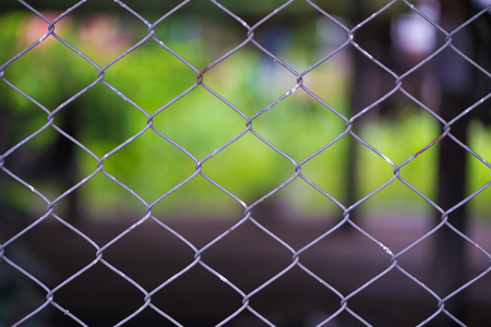 Rusty Chain Link Fence of steel netting on blur background. wired metal fence in vintage tone.