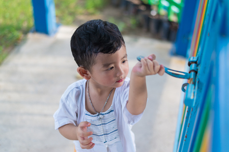Sad lonely Asian kid behind the grid or fence and trying to escape. shallow DOF