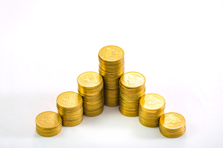 Savings, increasing columns of gold coins, piles of gold coins arranged as a graph on white background, business banking idea, shallow focus. Stock Photo