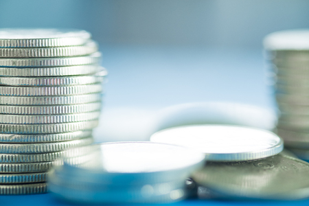 Piles of coins on working table with copy space, finance and business concept, shallow focus. Stock Photo