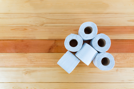 White tissues paper or toilet paper on brown wooden table with copy space.