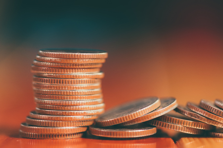 Stacks of coins on working table with copy space, finance and business concept, shallow focus. vintage tone.