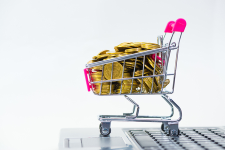 Shopping cart or supermarket trolley with laptop notebook on white background and copy space, e-commerce and online shopping concept.