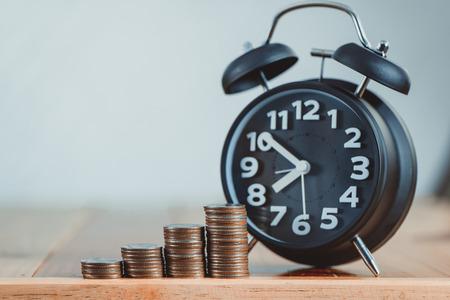目覚まし時計、作業テーブル、時間の節約お金のコンセプト、銀行、ビジネスのアイデアのコイン スタックのステップ。ビンテージ トーン。