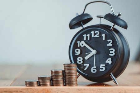 Réveil et étape de piles de pièces de monnaie sur la table de travail, le temps pour le concept d'argent de l'épargne, la banque et l'idée d'affaires. ton vintage.