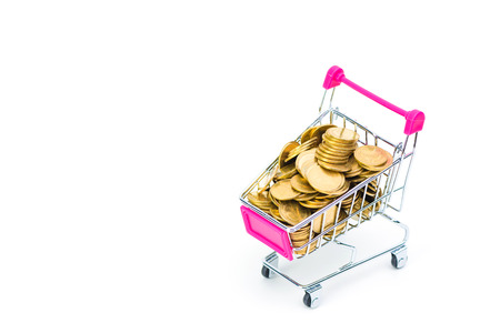 Stack of coins in shopping cart or supermarket trolley on white background, business finance shopping concept.