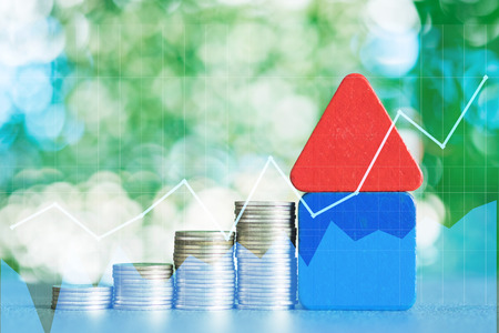 Double exposure of model house with step of coins stack and financial graph, real estate investment and saving banking money finance concept. Stock Photo