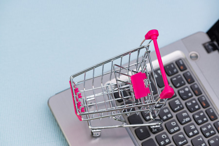 Shopping cart or supermarket trolley with laptop notebook, on grey background and copy space, e-commerce and online shopping concept.