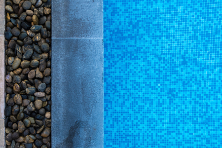 Edge of swimming pool with blue mosaic tiles at the bottom of the pool. poolside. Stock Photo