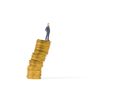 Figure miniature businessman or small people standing on unstable risky stack of coin on white background for money and financial business is not stable concept.