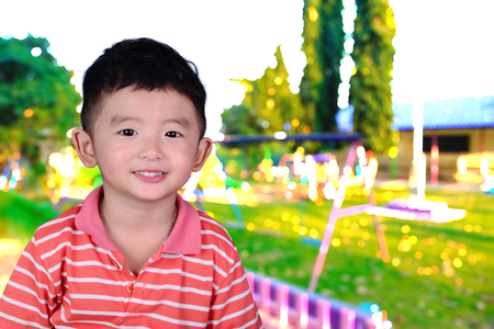 Double exposure of little Asian happy boy smile on blur image of playground background. kid concept.