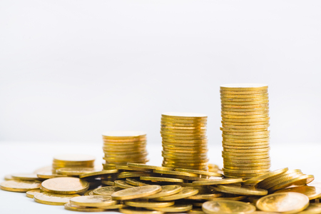 Savings, increasing columns of gold coins, piles of gold coins arranged as a graph on white background, business banking idea, shallow focus. Banco de Imagens