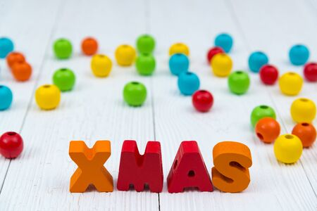 Xmas colorful wooden text on white wooden desk with Christmas decorations, Merry Christmas and happy new year concept, template for add text or photo. Stock Photo